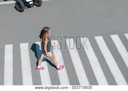 Stylish Child In Glasses, Fashion Clothes Walking Along Summer City Crosswalk. Kid On Pedestrian Sid