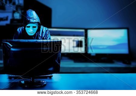 Anonymous Computer Hacker In White Mask And Hoodie. Obscured Dark Face Standing In The Middle And Ha