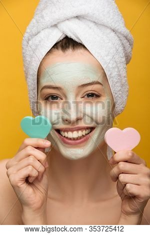 Cheerful Girl With Nourishing Mask On Face Holding Heart-shaped Cosmetic Sponges Isolated On Yellow