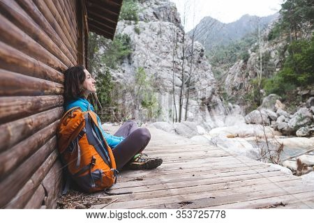 A Woman With A Backpack Sits On The Porch Of An Old Wooden House. The Traveler Found A Hut For An Ov