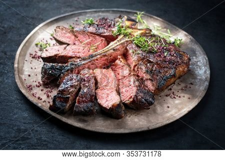 Barbecue dry aged wagyu porterhouse beef steak sliced with large fillet piece with herbs and red salt as closeup on a modern design rustic plate
