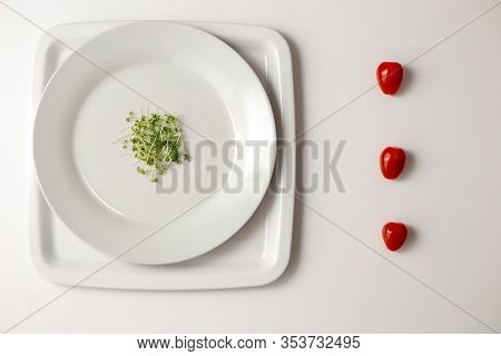 Green Watercress On A Round White Plate And Fresh Three Red Cherry Tomatoes Side View In A Row