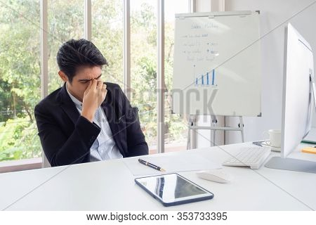 Businessman Sit At A Desk In An Office Green Trees. He With His Hand Holding His Face Feel Sad, Worr