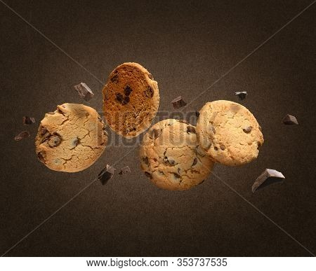Flying Chocolate Chip Cookies With Pieces Of Chocolate On Dark Brown Background.