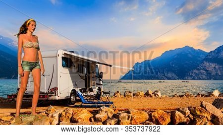 Europe travel attractive tourist girl in camping ground with camper, italian summer vacation. Beautiful young happy blonde girl in swimsuits on the beach at Garda Lake.