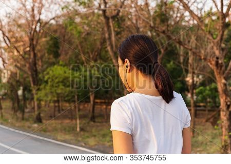 Woman Exercise Walking In The Park Listening To Music With Earphone.