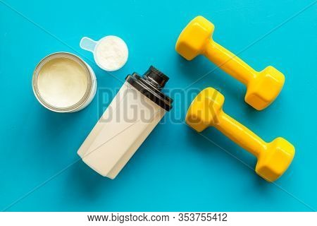 Sport Nutrition. Whey Protein, Shaker, Dumbbells On Blue Background Top-down Flay Lay