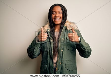 Young african american woman wearing winter parka coat over isolated background success sign doing positive gesture with hand, thumbs up smiling and happy. Cheerful expression and winner gesture.
