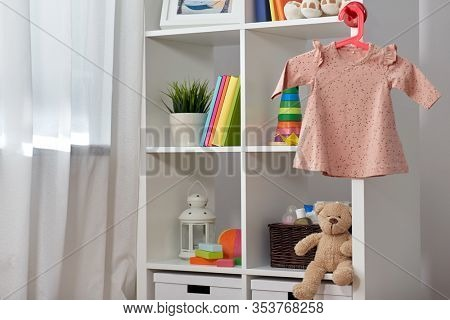 kid's room, interior and home concept - white bookcase with books, toys and pink dress for baby girl on hanger