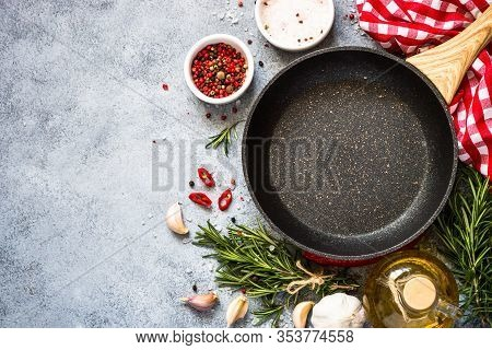 Food Cooking Background With Frying Pan Or Skillet, And Herbs On Gray Stone Table. Top View With Cop