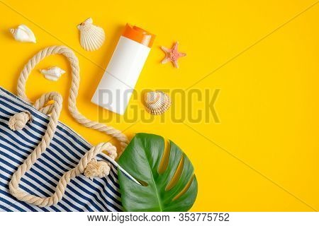 Sunblock Cream Lotion Bottle Mockup, Striped Beach Bag And Tropical Leaves On Yellow Background. Sum