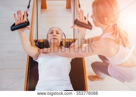View From Above Female Senior Patient Workout Her Arms, Hands Pilates Reformer. Pilates Insrtuctor W
