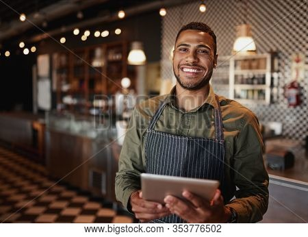 Young African-american Man Wearing Apron Standing Using Digital Tablet In Coffee Shop