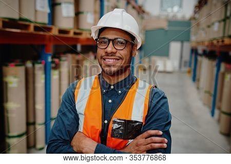 Portrait Of Handsome Cheerful Supervisor In Warehouse Standing With Folded Hands With Material While