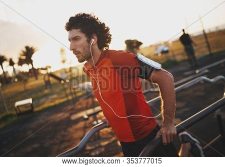 Portrait Of A Athletic Young Man Listening To Music On Earphones Exercising On An Outdoor Fitness Pa