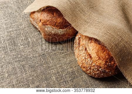 Two Loaves Of Rustic Bread Lie On A Burlap Buried In A Cloth Of Burlap With Pestle For Text. The Con