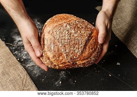 A Man Holds In His Hands A Loaf Of Rustic Organic Bread. The Concept Of A Rural Bakery.