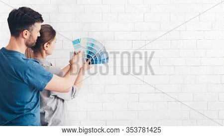 Embracing Happy Young Couple Choosing Color With Palette For Inner Bricks Wall, Panorama, Copy Space
