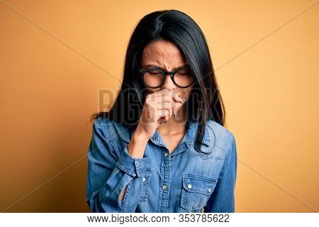 Young beautiful chinese woman wearing casual denim shirt over isolated yellow background feeling unwell and coughing as symptom for cold or bronchitis. Health care concept.