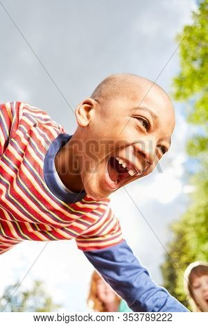 African boy plays with enthusiasm with his friends in summer