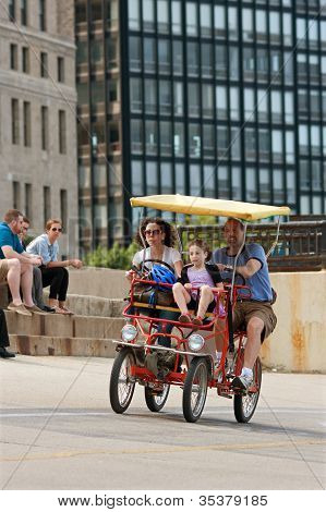 Tourist Family Pedals Four-wheeled Cycle Along Lake Shore Drive