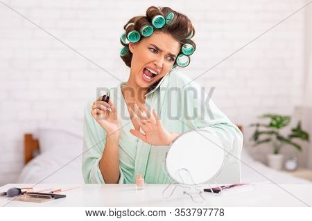 Housewifes Lifestyle. Woman With Curlers Talking On Phone Doing Nails Sitting In Bed At Home. Select