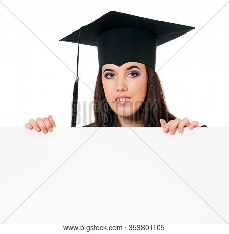 Female graduate student peeking from behind a blank panel, isolated on white background. Beautiful graduate teen girl student in mantle showing blank placard board.