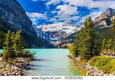 Glacial Lake Louise in Banff Park in Canada, Canadian Rockies. Pebble lake embankment. Lake with azure water is surrounded by forests and mountains. The concept of ecological,active and photo tourism