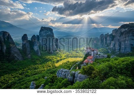 Sunset over monastery of Rousanou and Monastery of St. Nicholas Anapavsa in famous greek tourist destination Meteora in Greece on sunset with sun rays and lens flare and dramatic sky