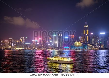 Hong Kong skyline cityscape downtown skyscrapers over Victoria Harbour in the evening illuminated with tourist boat ferries . Hong Kong, China