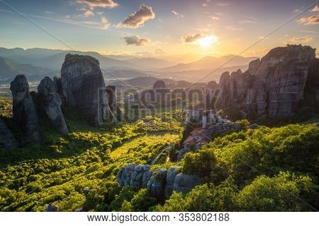 Sunset over monastery of Rousanou and Monastery of St. Nicholas Anapavsa in famous greek tourist destination Meteora in Greece on sunset with sun rays and lens flare