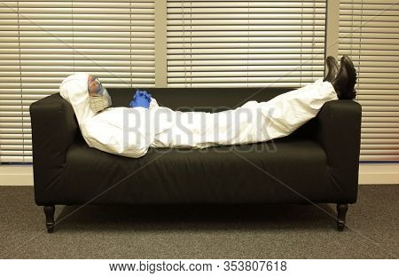 Quarantine - home arrest. Professional in protective uniform and mask, lying on the sofa, waiting  and doing nothing