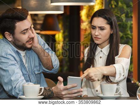 Infidelity Concept. Jealous Girlfriend Pointing Finger At Cheating Boyfriends Phone Demanding Explan