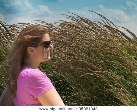Closeup Side View Of Smiling Young Woman With Tall Grass Blowing In The Wind