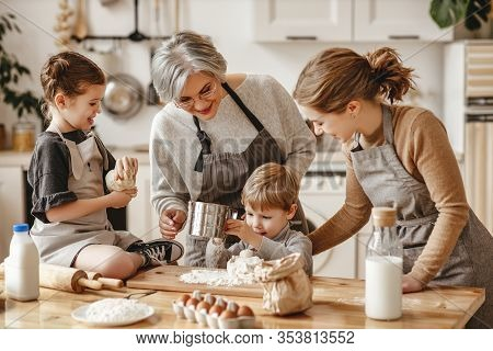 Happy Family A Grandmother With Her Daughter And Grandchildren Cooks In Kitchen, Kneads Dough And Ba