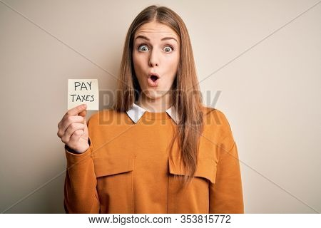 Young beautiful blonde woman holding pay taxes to goverment reminder over yellow background scared in shock with a surprise face, afraid and excited with fear expression