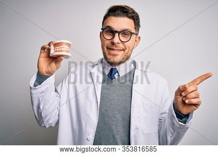 Young dentist man with blue eyes holding orthodontic dental prosthesis over isolated background very happy pointing with hand and finger to the side