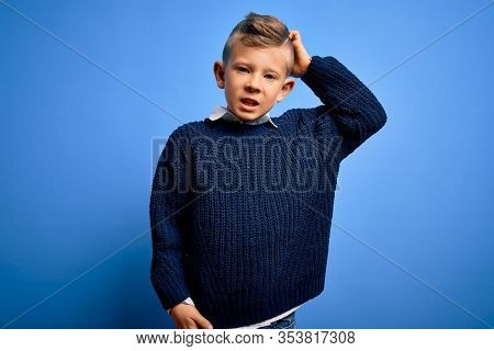 Young little caucasian kid with blue eyes wearing winter sweater over blue background confuse and wonder about question. Uncertain with doubt, thinking with hand on head. Pensive concept.