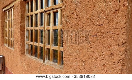 Wooden Windows In Adobe House Or Clay House. An Old Clay Wall With Straw