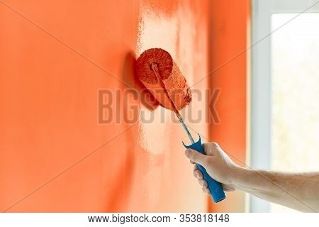 Male Hand Painting Wall With Paint Roller. Painting Apartment, Renovating With Red Orange Color Pain