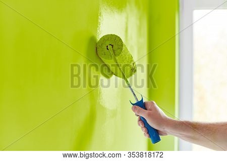 Male Hand Painting Wall With Paint Roller. Painting Apartment, Renovating With Spring Green Color Pa