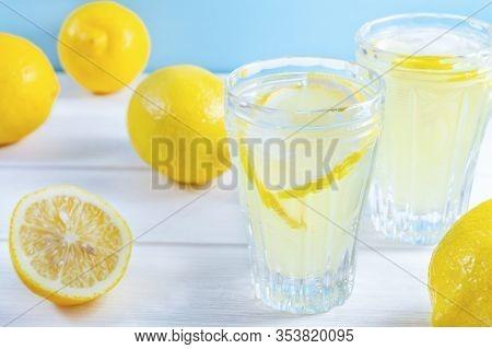 Glasses With Summer Drink Lemonade And Lemon Fruit On White Wooden Table.