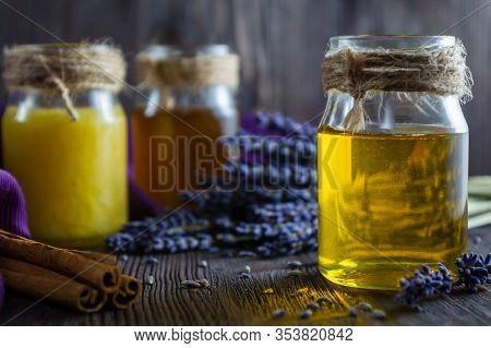 Lavender And Herbal Honey In Glass Jars And Lavender Flowers On Dark Wooden Background.