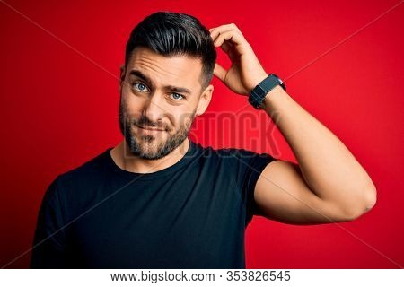 Young handsome man wearing casual black t-shirt standing over isolated red background confuse and wonder about question. Uncertain with doubt, thinking with hand on head. Pensive concept.