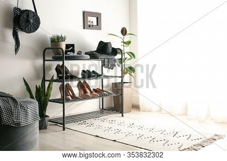 Black Shelving Unit With Shoes And Different Accessories Near White Wall In Hall
