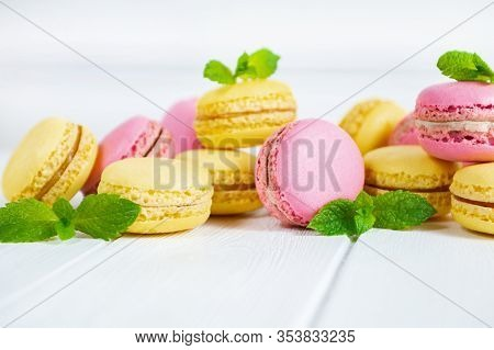 Colorful Macaroons And Mint Leaves On White Wooden Background.