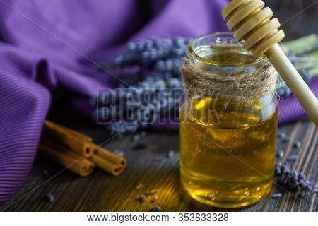 Lavender And Herbal Honey In Glass Jar With Honey Spoon On Dark Wooden Background.