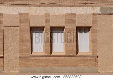 A Set Of Retro Old Windows In A Brown Brick Warehouse Office Building With Deep Shadows