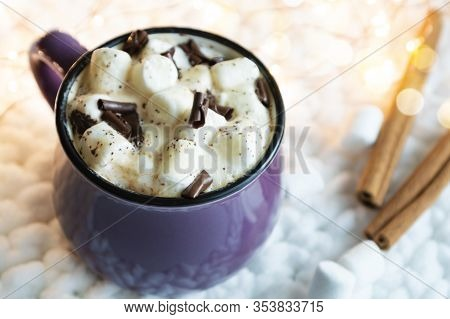 Hot Cocoa With Marshmallows In Ceramic Mug, And Cinnamon Sticks, On Knitted Fabric Background. Cozy