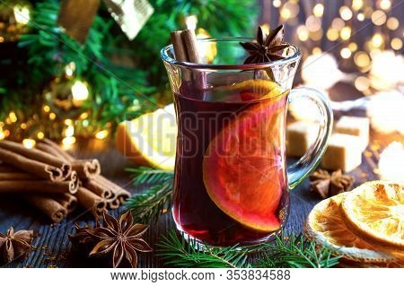 Christmas Mulled Red Wine With Spices And Oranges On Old Wooden Table. Traditional Hot Drink At Chri